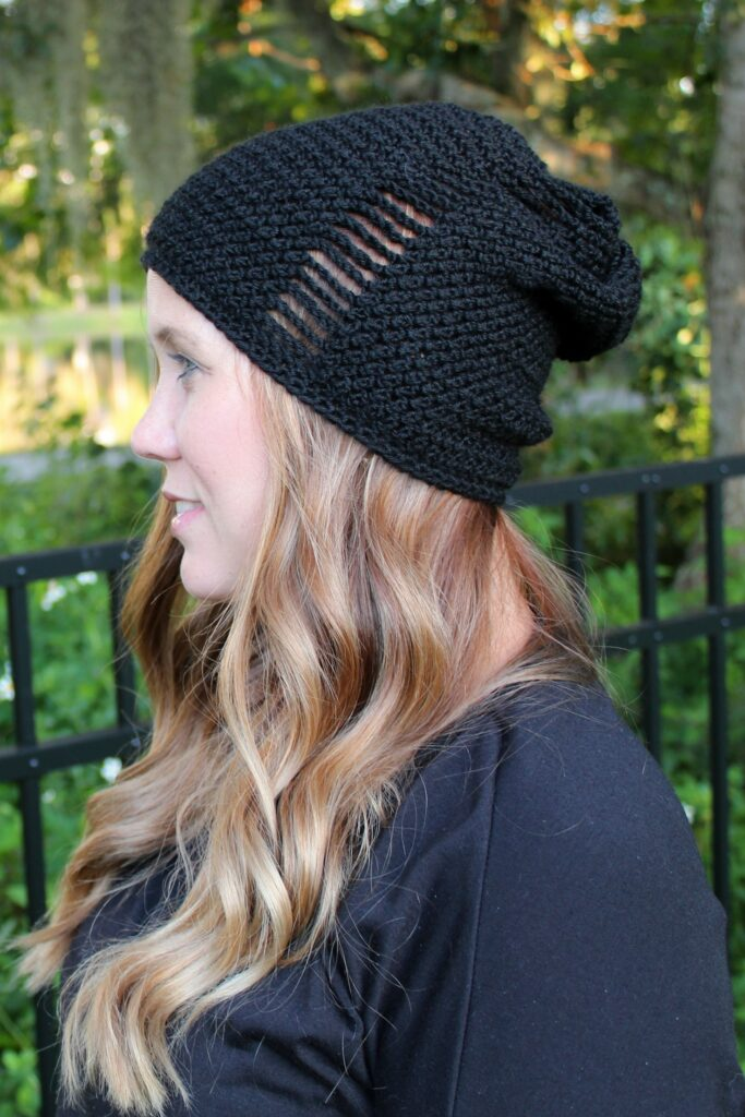 Woman wearing a black crochet slouch hat, called the La Maille Hat.