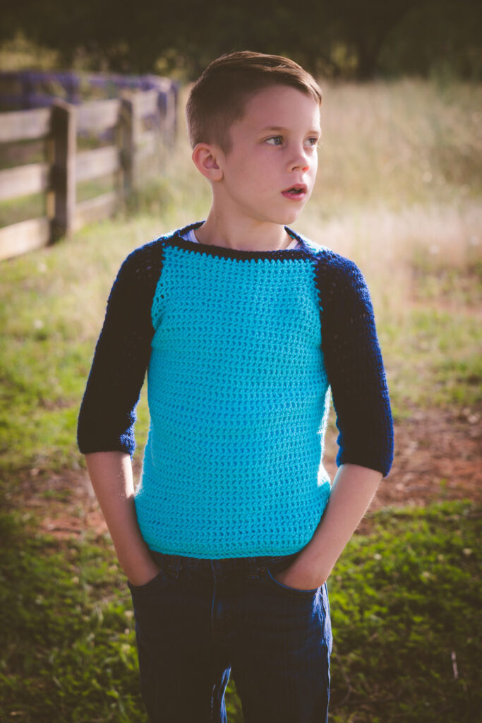 Child wearing a blue crochet sweater, called the Parker Baseball Tee.