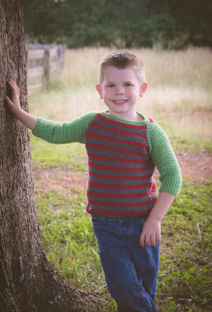 Child wearing crochet sweater called the Parker Baseball Tee.