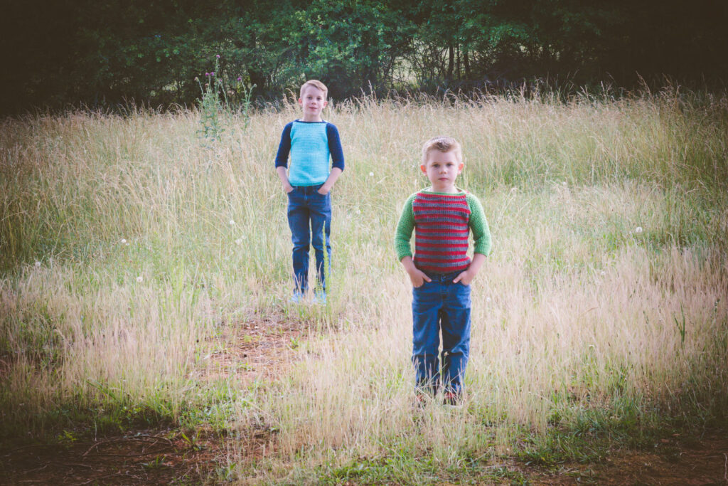 Two boys standing in a field, both wearing a crochet sweater for kids, called the Parker Baseball Tee.
