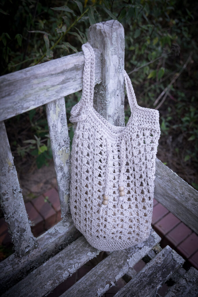 Close up of a tan colored crochet bag, called the Katie Tote. This bag features open v-stitches, simple handles, and a drawstring with wooden beads at the end.