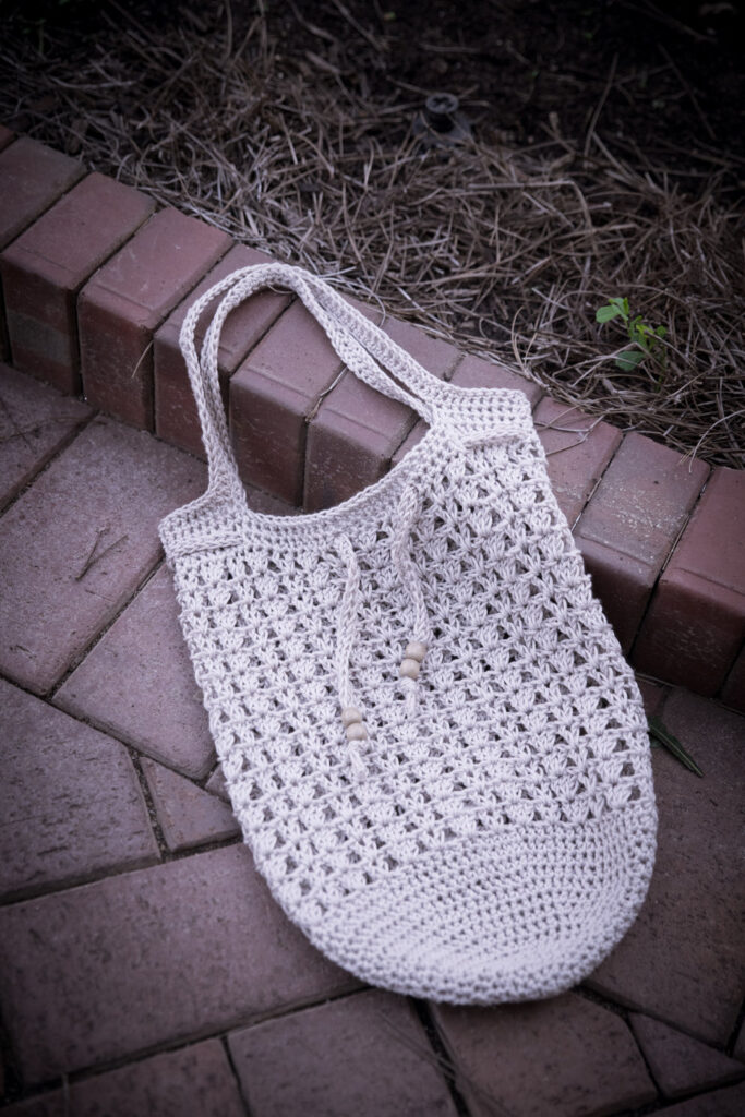 Crochet tote bag, called the Katie Tote,  lying flat on the ground.