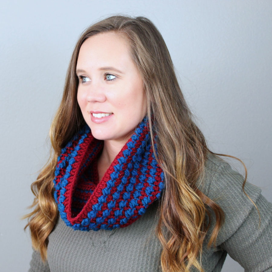 Woman wearing a dark red and blue crochet cowl, called the Tuscan Sun Cowl.