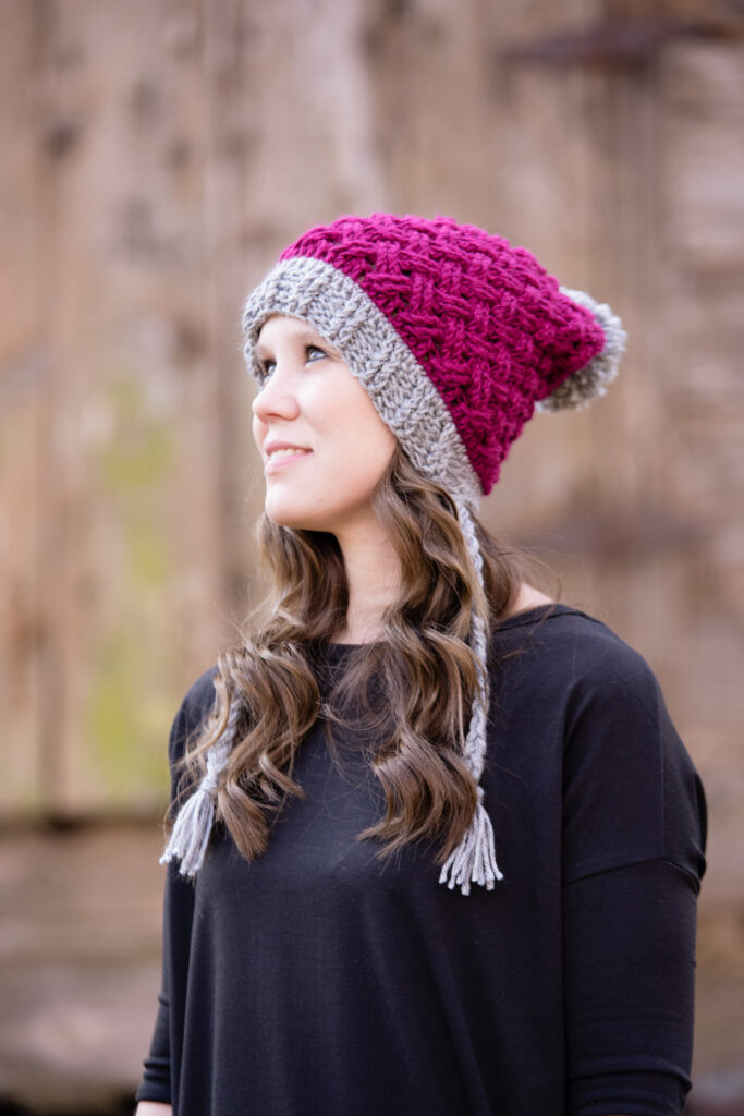 Woman wearing a pink and gray Celtic Weave crochet hat with braided tassels and a gray pom pom.
