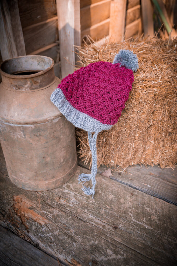 Celtic Weave Crochet Hat in pink and gray colors laid on a bail of hay.