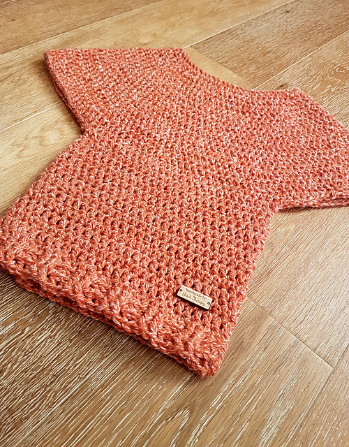 Flat lay photo of an orange colored dolman sleeve crochet sweater, called the Victoria Sweater.