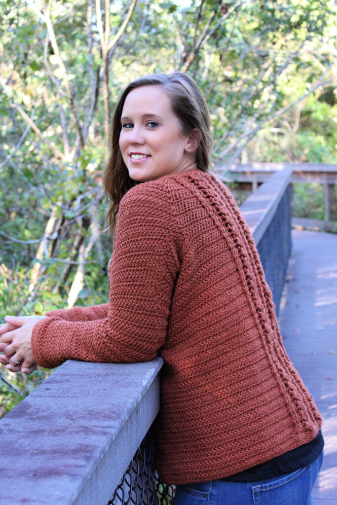 Woman learning against a bridge wearing a crochet cardigan called the Aspen Cardigan.