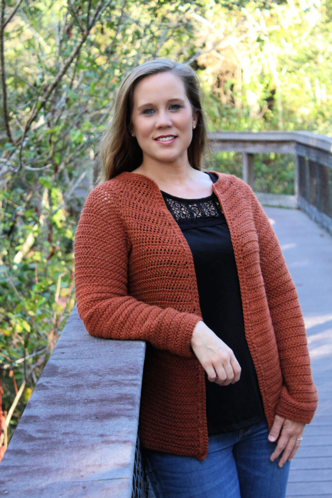 Woman wearing dark orange crochet cardigan pattern called the Aspen Cardigan.