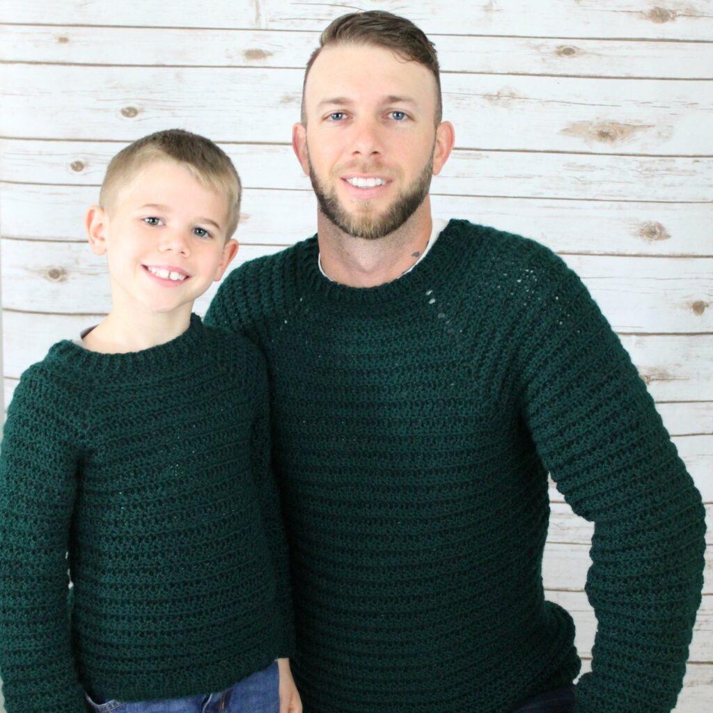 A Father and Son both wearing a crochet pullover sweater, called the Dude Sweater.