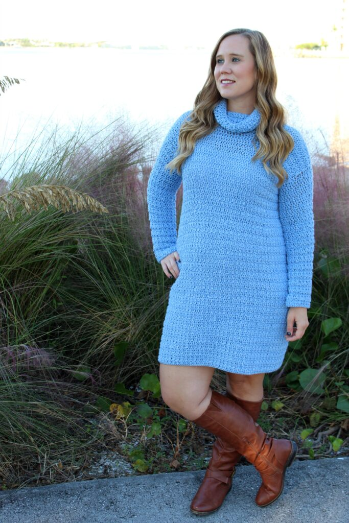 Woman wearing blue crochet dress, called the Edgewater Sweater Dress.