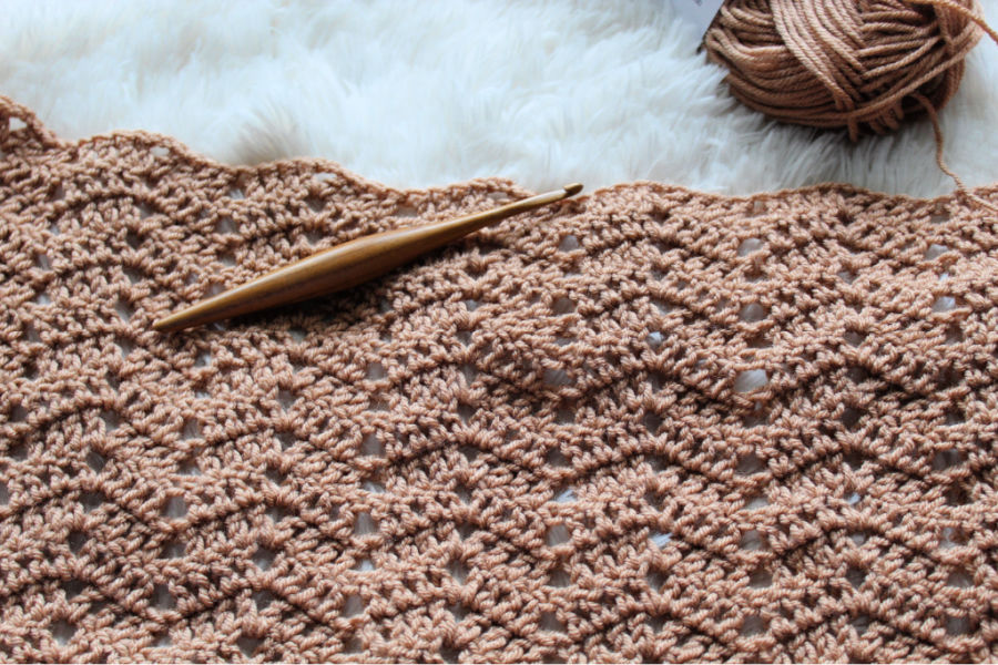 A crochet project with a Furls Streamline crochet hook laid on top of the yarn.