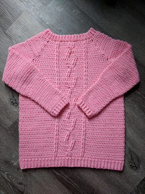 Flat lay of a crochet sweater with cables, called the Crossroads Sweater.