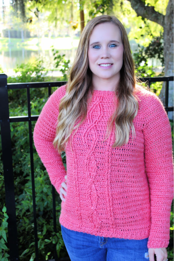 Woman wearing a pink crochet sweater, called the Crossroads Sweater.
