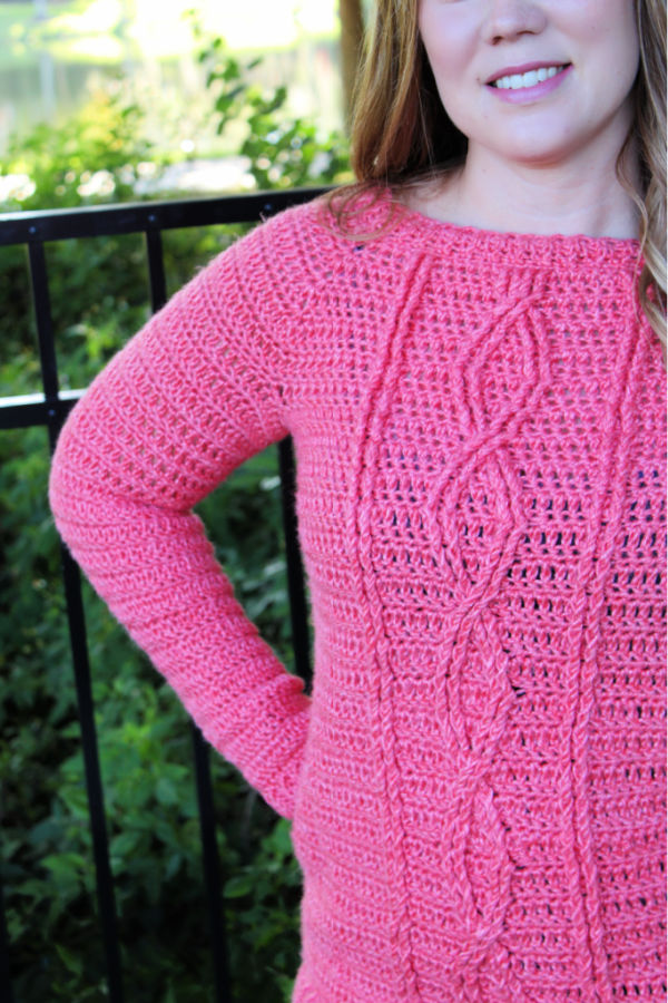Close up of woman wearing a pink crochet sweater with cables. This sweater is called the Crossroads Sweater.