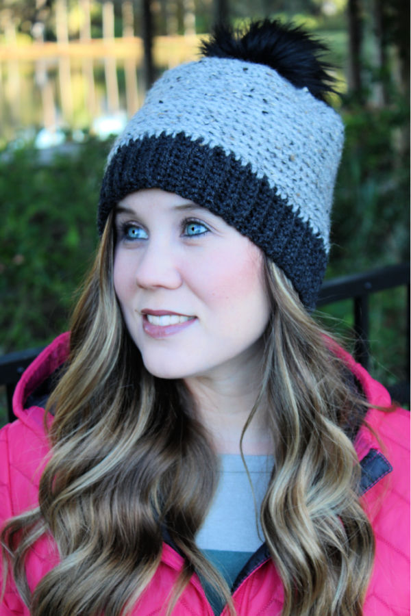 Woman wearing a gray and black camel stitch crochet beanie.