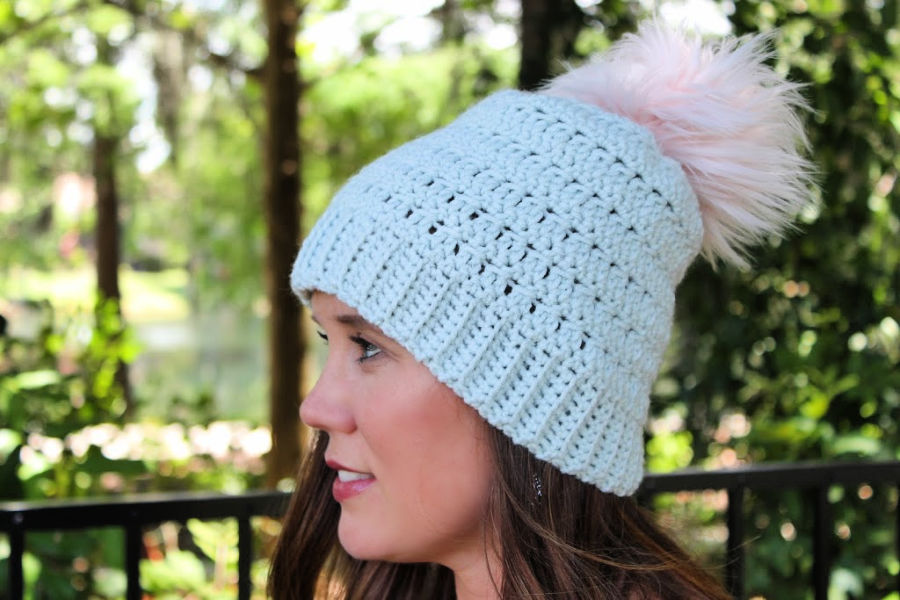 Woman wearing a light blue crochet hat with a light pink pom on the top. This hat is called the Rory Hat.