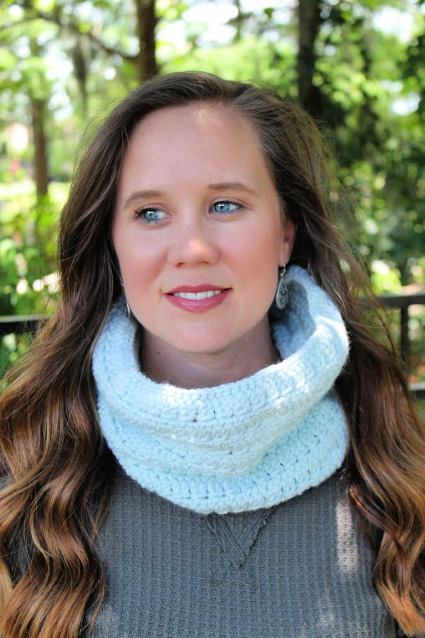 Woman wearing a light blue crochet cowl, called the Rory Cowl.