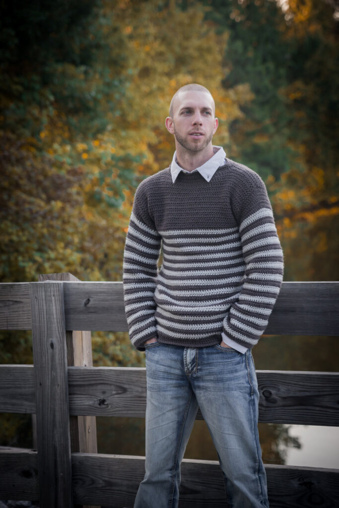 Man wearing a men's crochet sweater called the Upper Eastside Sweater. He is leaning against a fence with a lake and fall foliage behind him.