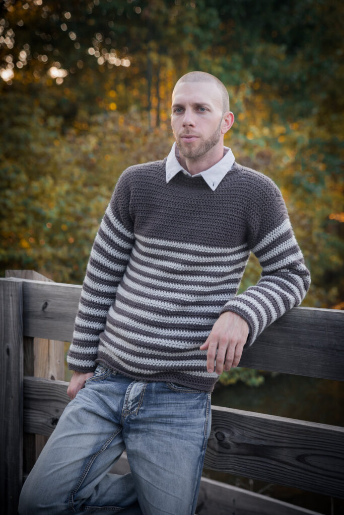 Man leaning against a fence, wearing a men's crochet sweater called the Upper Eastside Sweater.