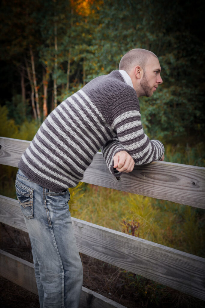 Man learning over a fence, wearing a men's crochet sweater called the Upper Eastside Sweater.