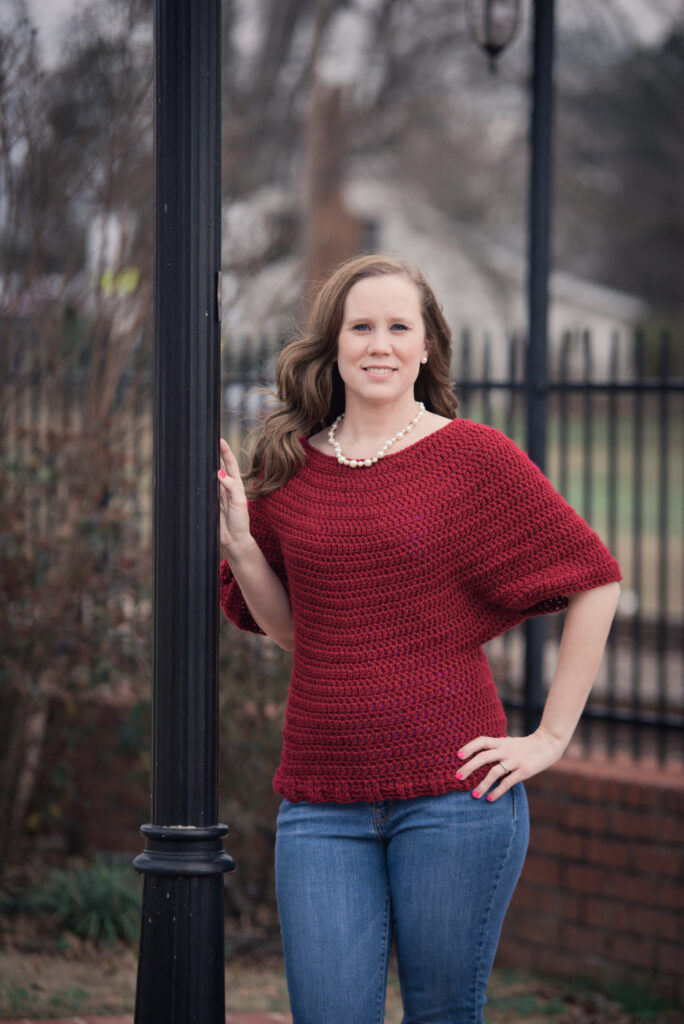 Woman wearing a dark red dolman sleeve crochet sweater, called the Victoria Sweater.
