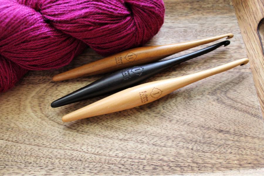 Three Furls Streamline Crochet Hooks lying next to a skein of pink yarn.