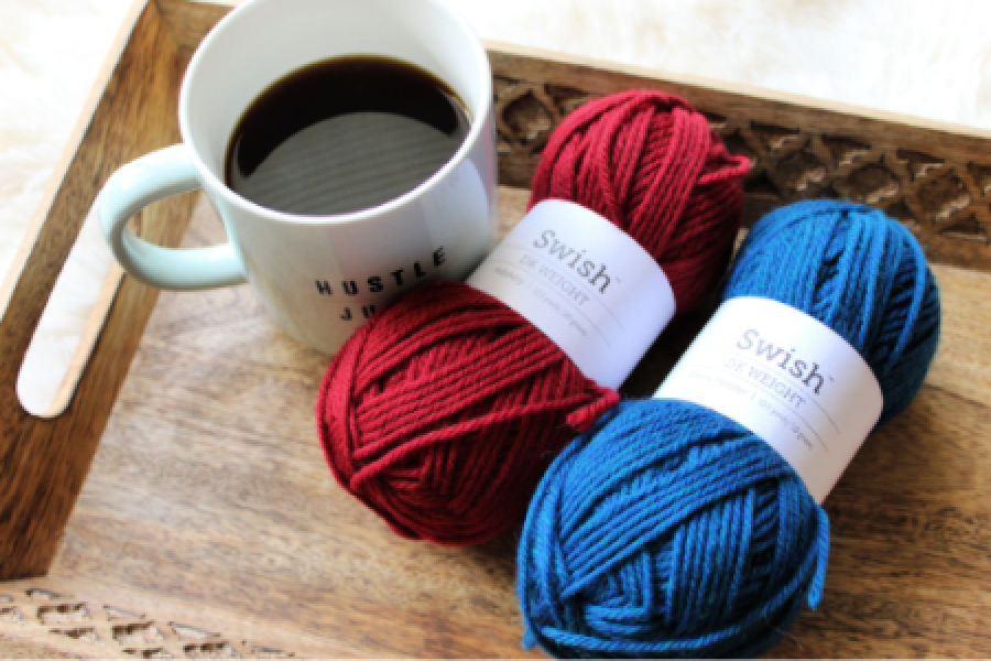 Two skeins of Swish DK yarn on a wooden tray next to a cup of coffee.