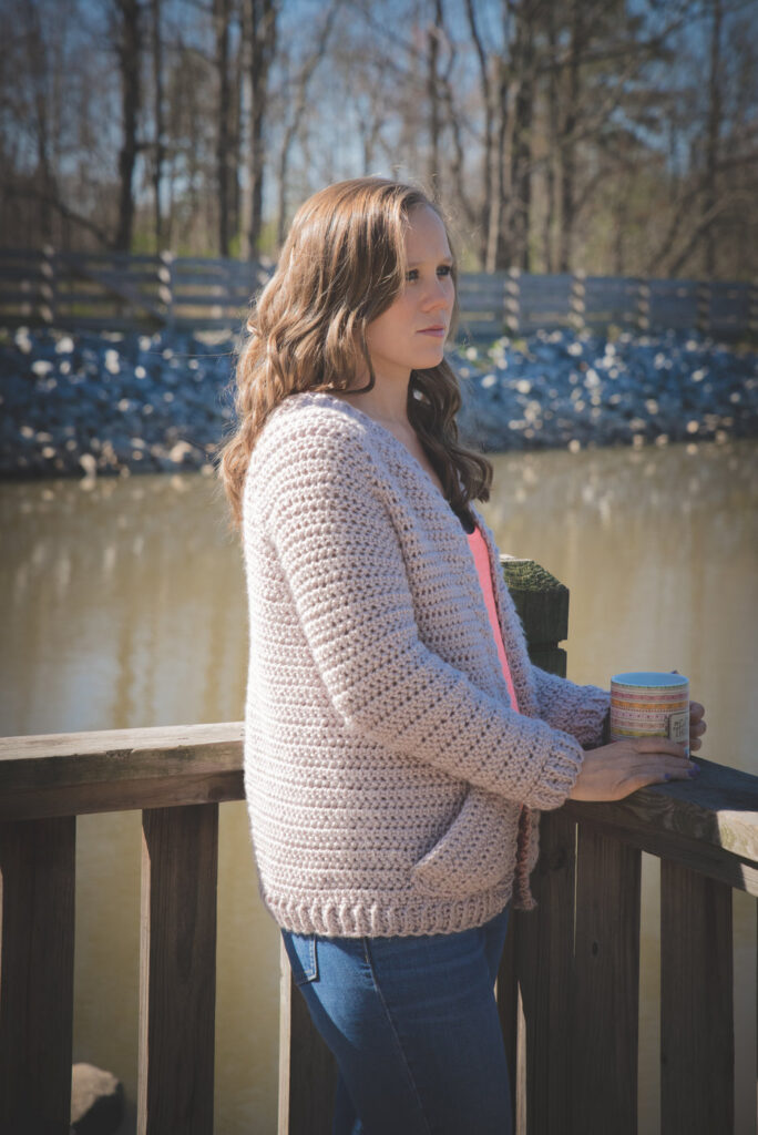 Woman looking over a lake, wearing a chunky crochet cardigan with pockets. This cardigan is called the Charlotte Cardigan.