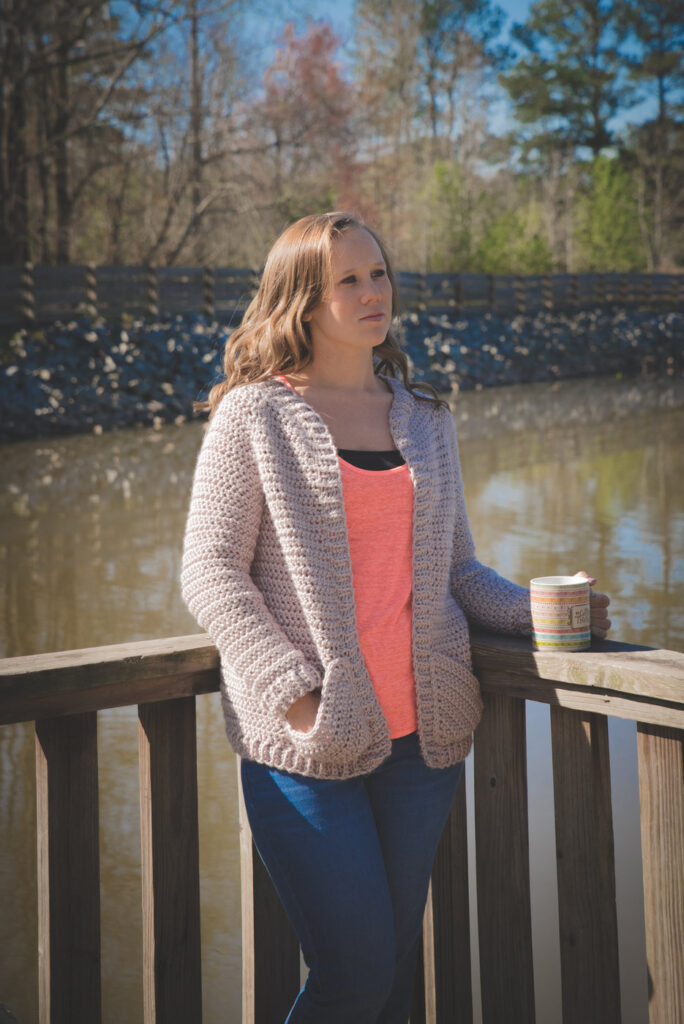 Woman wearing a chunky crochet cardigan, called the Charlotte Cardigan.