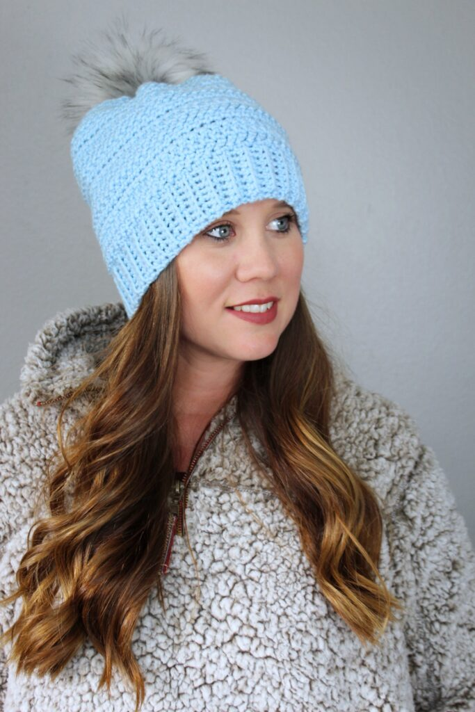 Woman wearing a light blue crochet hat called the Hope Hat.