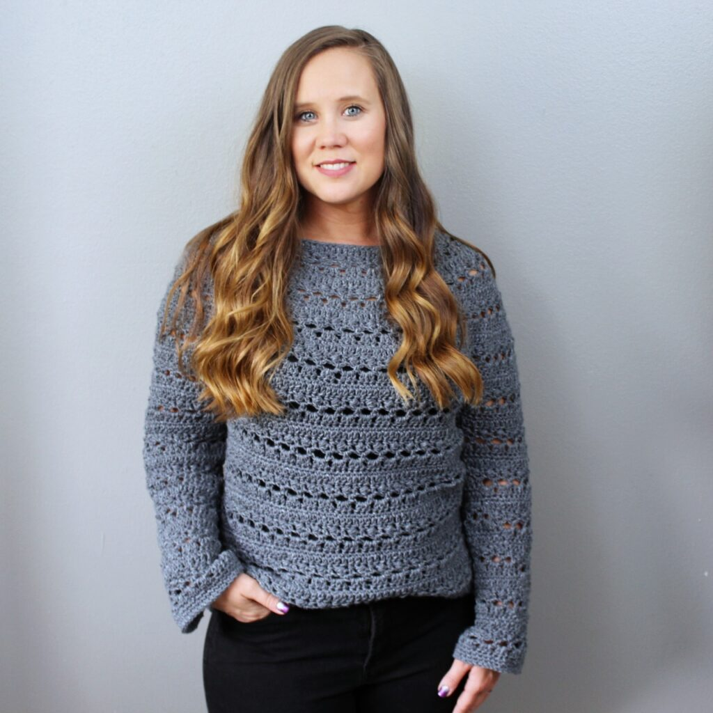 Woman wearing a great crochet sweater, called the Brimstone Sweater.