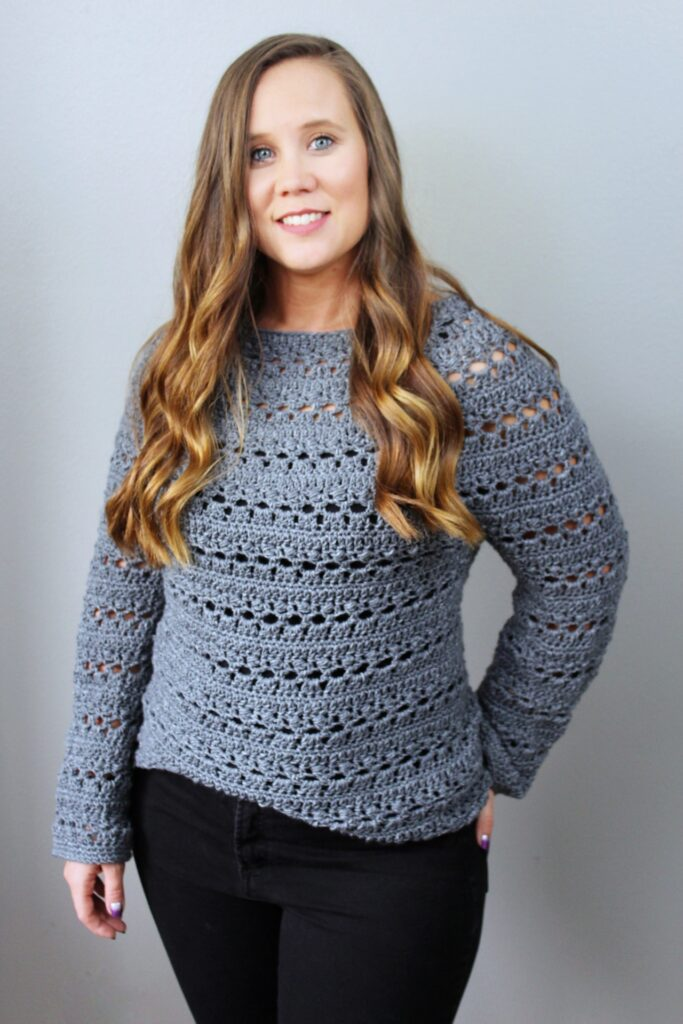 Woman wearing a gray crochet sweater, called the Brimstone Sweater.