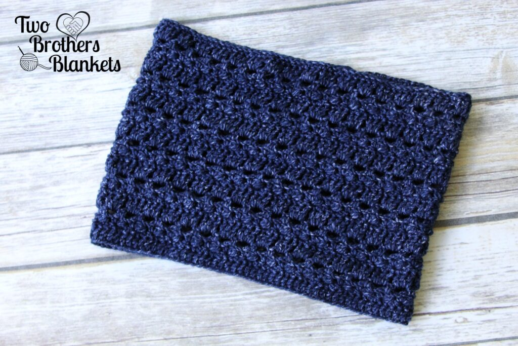 Flat lay photo of a blue crochet cowl, called the Brimstone Cowl.