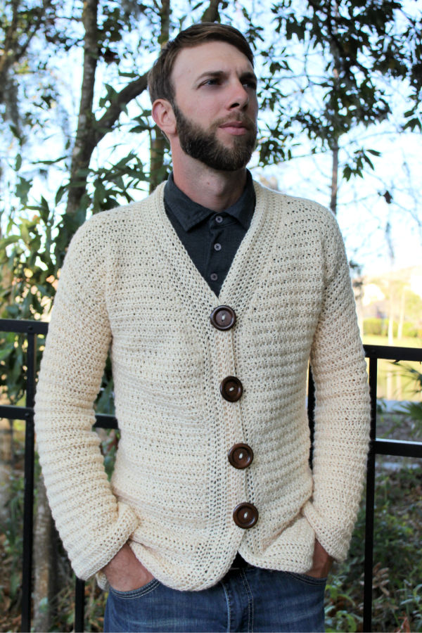 Man wearing a cream colored crochet cardigan, called the Dude Cardigan