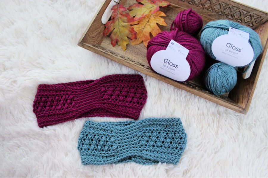 Flat lay photo of two crochet earwarmers with a tray of yarn and fall leaves lying next to them.