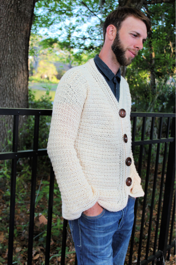 Man wearing a cream colored crochet cardigan, called the Dude Cardigan.
