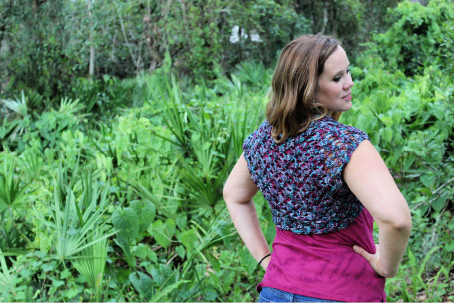 Woman wearing a crochet shrug called the Nova Shrug. It is purple and blue with a shell stitch combination.