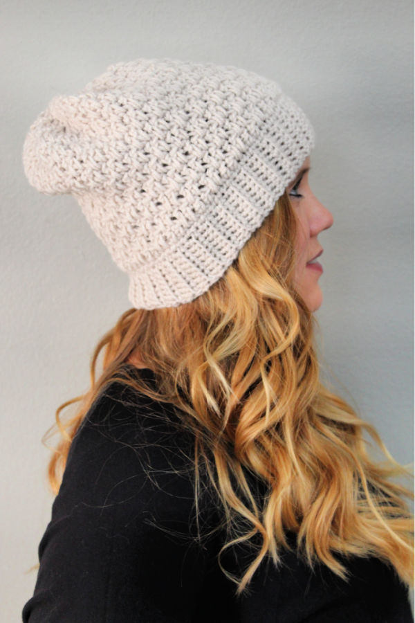 Woman wearing a cream colored crochet hat, called the Michelle Hat.