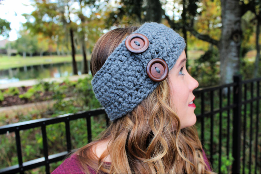 Side view of woman wearing gray crochet earwarmer pattern with large brown buttons.
