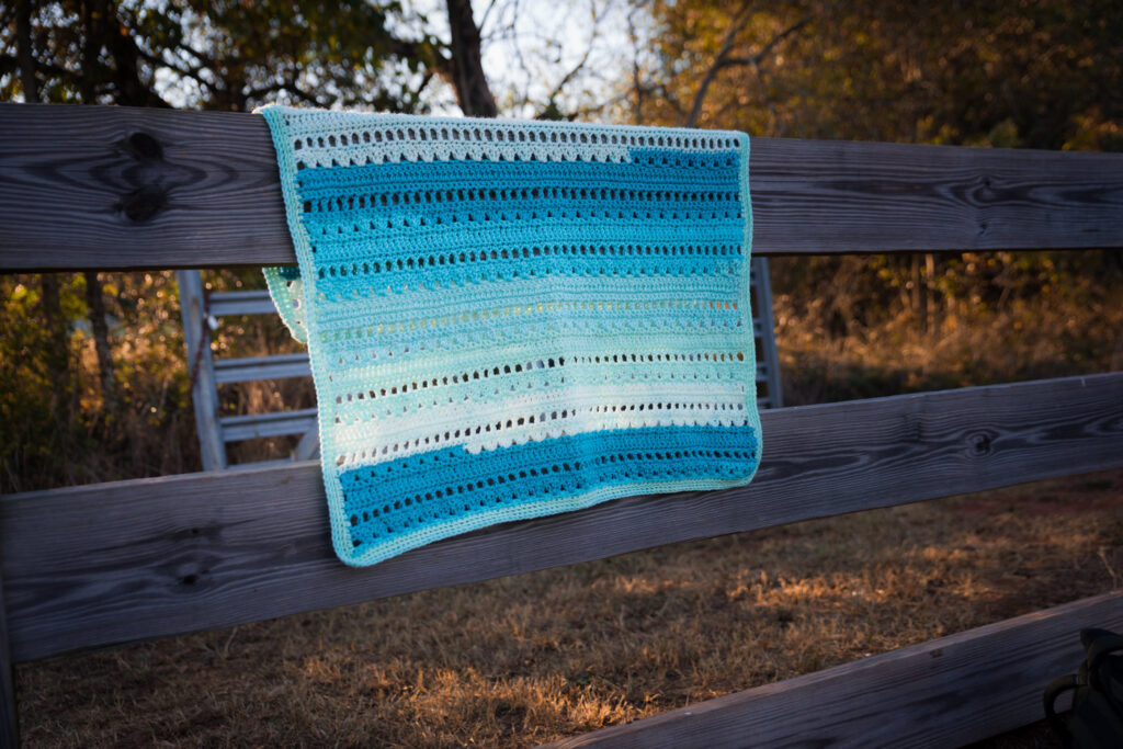 Blue crochet baby blanket pattern laid over a wooden fence in a park.