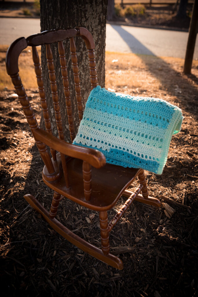 Blue crochet baby blanket folded up and sitting on a small wooden rocking chair.