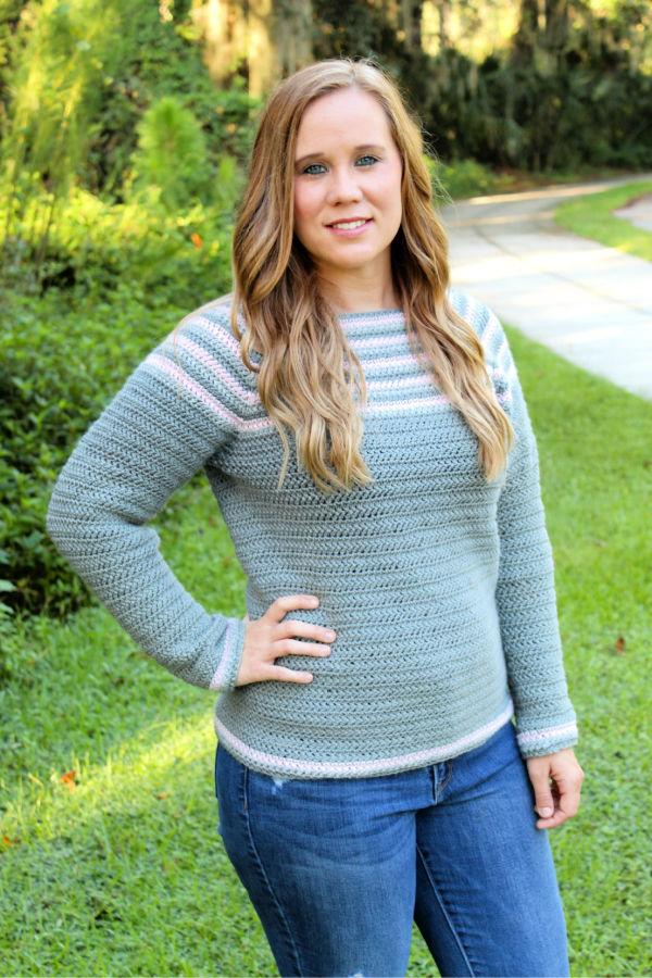 Woman wearing a gray and pink crochet raglan sweater, called the Remi Raglan.