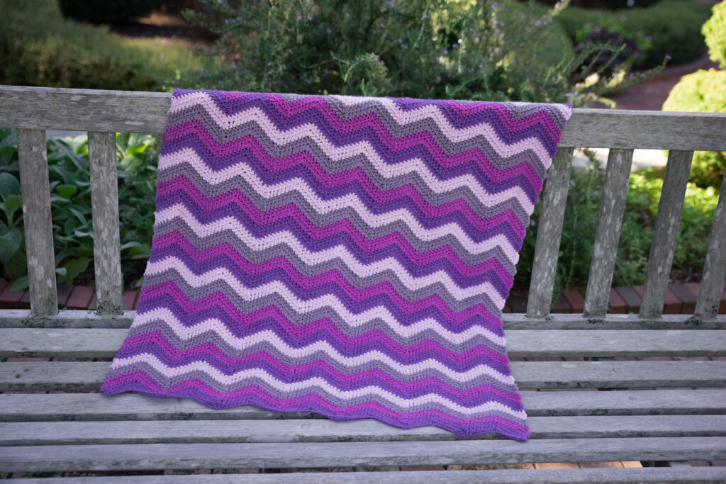 Chevron Crochet Blanket, made in 4 shades of purple, called the Happy Herringbone Chevron Blanket.
