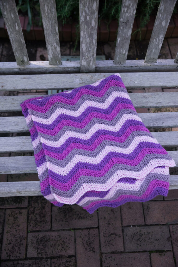 Close up of the chevron crochet blanket, called the Happy Herringbone Chevron Blanket,  folded on a park bench.