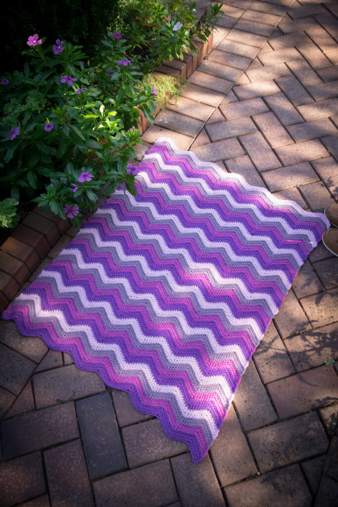 A chevron crochet blanket, called the Happy Herringbone Chevron Blanket, laid flat on the ground.