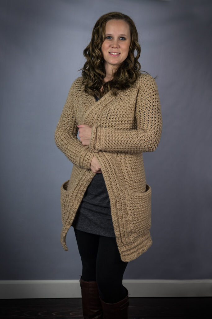 Woman wearing a tan colored crochet cardigan, called the Kristen Cardigan.