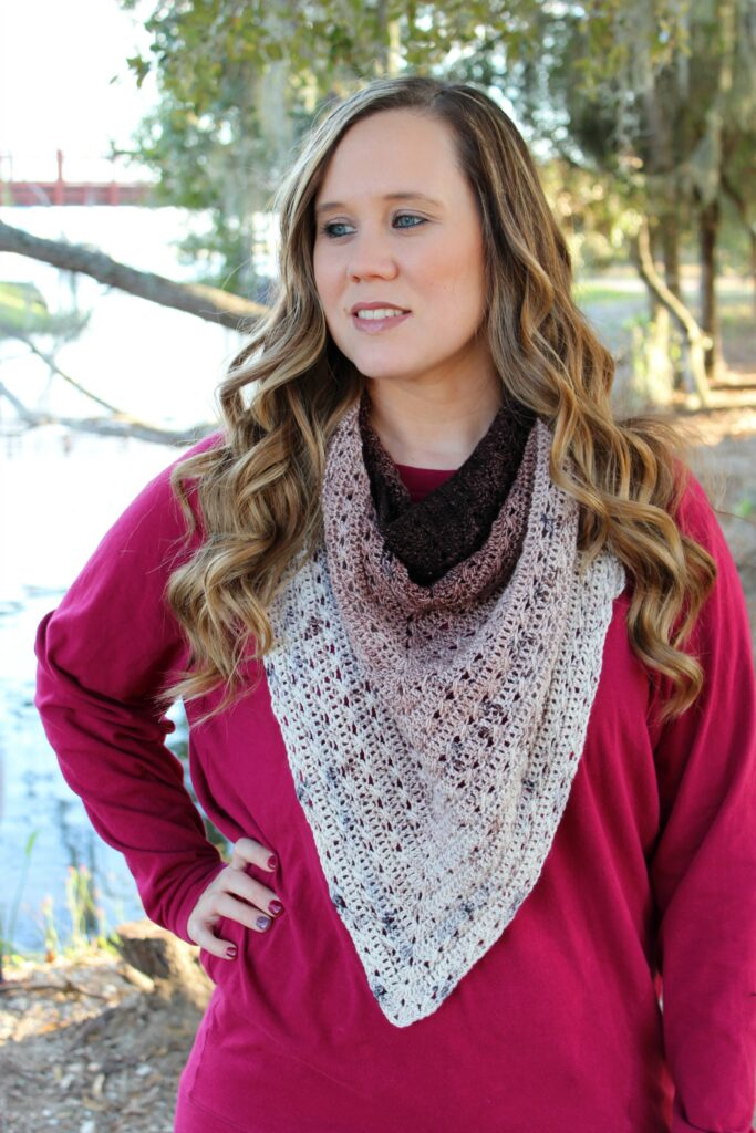 Woman wearing a brown and cream colored crochet triangle shawl, called the Sweet Tea Shawl.