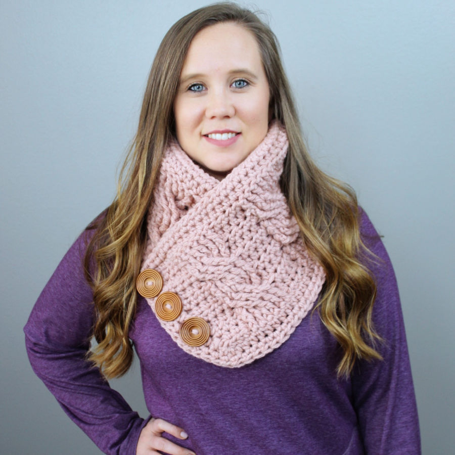 Woman wearing a pink crochet cowl with buttons. This cowl is called the Alexis Cowl.