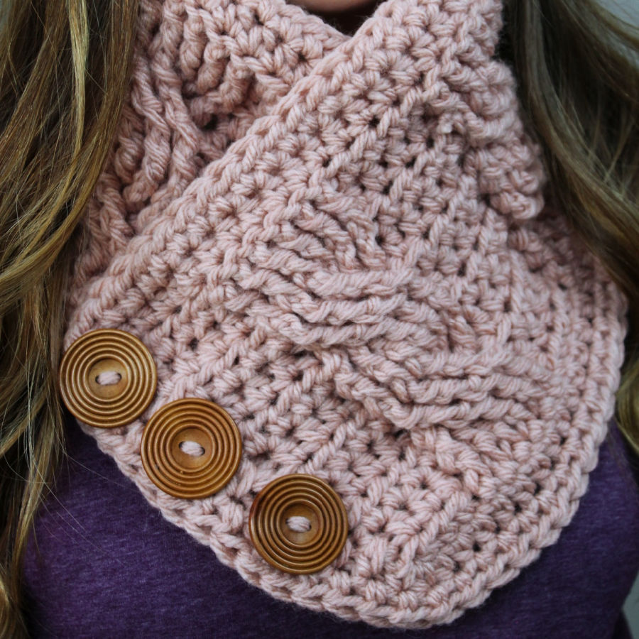 Close up of a pink crochet cowl with large buttons and cable stitching.