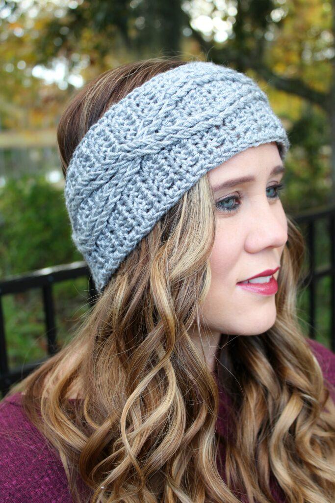 Woman wearing a light gray crochet headband, called the Crossroads Headband.